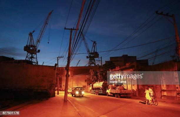 People walk in front of a shuttered shipyard in the Caju neighbourhood which houses two forlorn shipyards along Guanabara Bay on August 8 2017 in Rio...