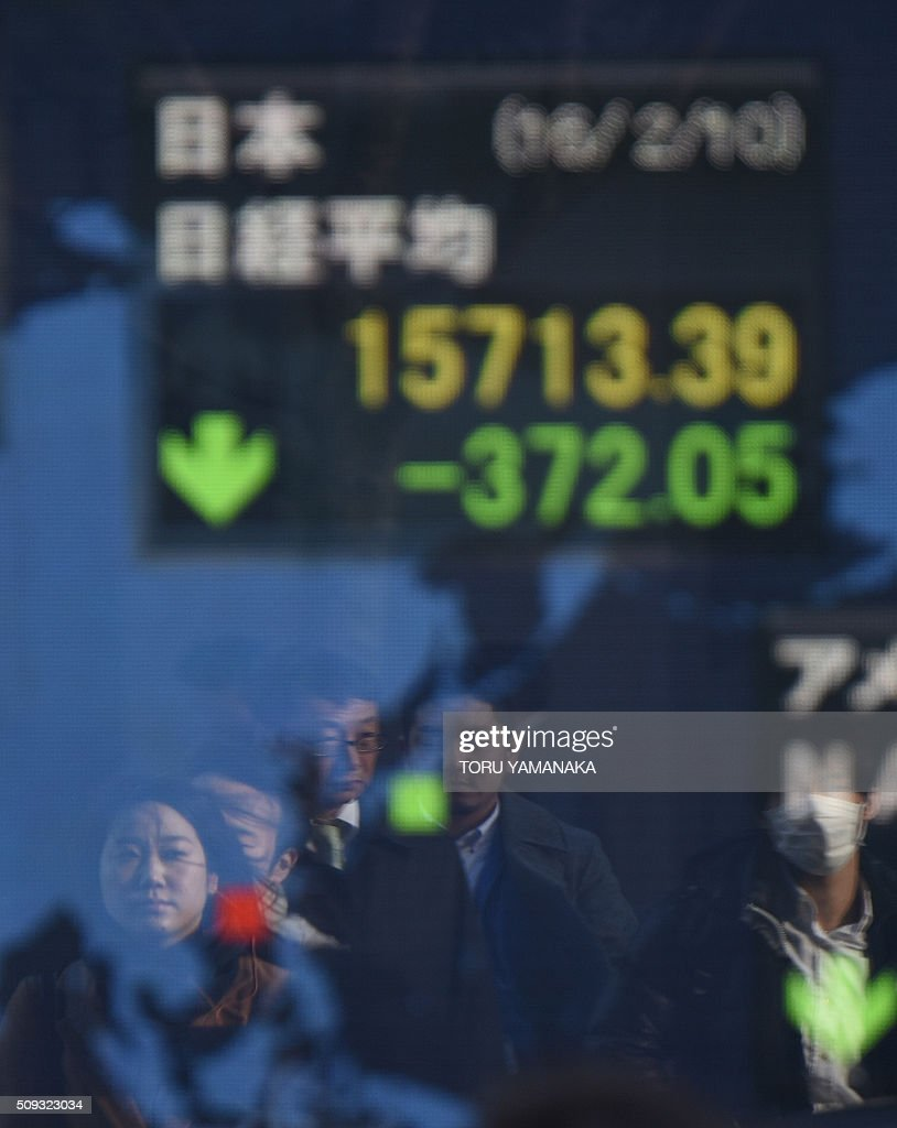 People walk in front of an electric quotation board flashing the Nikkei key stock index of the Tokyo Stock Exchange (TSE) in front of a securities company in Tokyo on February 10, 2016. Tokyo stocks again dropped on February 10 to their lowest level since late 2014, as fears of a global recession hammered investor confidence ahead of testimony by the head of the US central bank. AFP PHOTO / Toru YAMANAKA / AFP / TORU YAMANAKA