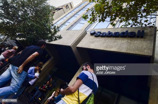 People walk in front of 'Banc Sabadell' new headquarters in Alicante on October 6 2017 Banc Sabadell Catalonia's secondbiggest bank said today it was...