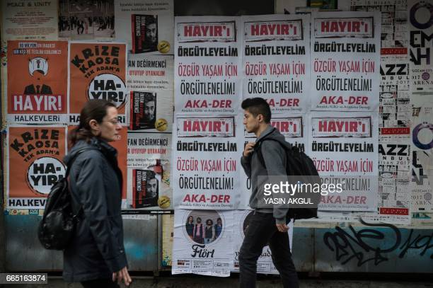 People walk in front of 'NO' banners on April 6 2017 in Istanbul 10 days ahead of the referendum on whether to change the current parliamentary...