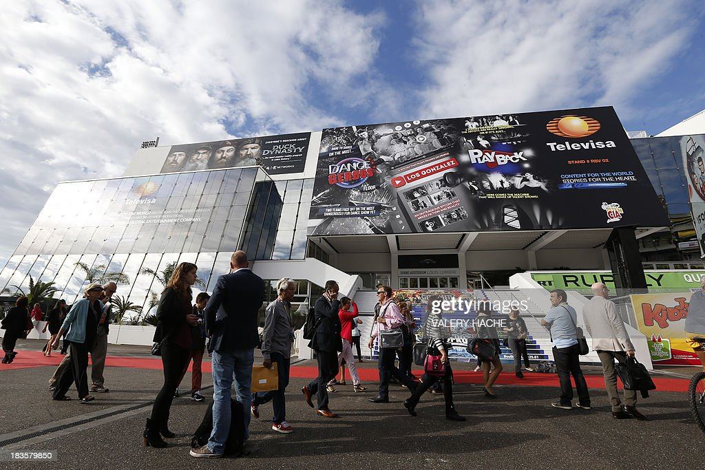 People walk in front of 'Palais des Festivals' during the MIPCOM audiovisual trade fair on October 7, 2013 in Cannes, southeastern France. AFP PHOTO / VALERY HACHE