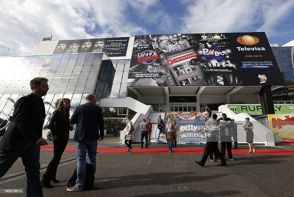People walk in front of 'Palais des Festivals' during the MIPCOM audiovisual trade fair on October 7, 2013 in Cannes, southeastern France.