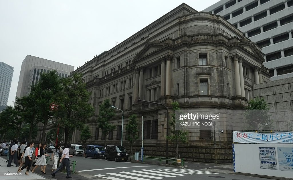 People walk in front of the Bank of Japan headquarters in Tokyo on July 1, 2016. Japan was clobbered with a one-two punch July 1 morning as weak data and a lacklustre business confidence report underscored the slowdown dragging on the world's number three economy. / AFP / KAZUHIRO