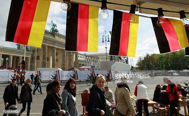 People walk in front of the Brandenburg Gate and by German flags at an outdoor kiosk set up for the upcoming unity celebration on October 1 2010 in...