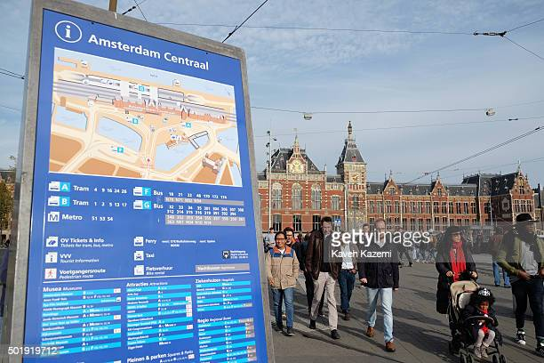 AMSTERDAM NETHERLANDS OCTOBER 30 2015 People walk in front of the central station passing a blue board with indication of transport facilities on...