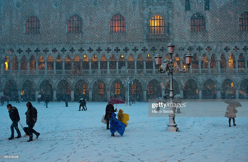 People walk in front of the Doge Palace under heavy snow on February 11, 2013 in Venice, Italy. Heavy snow, High water, wind and rain has been forcasted for today.