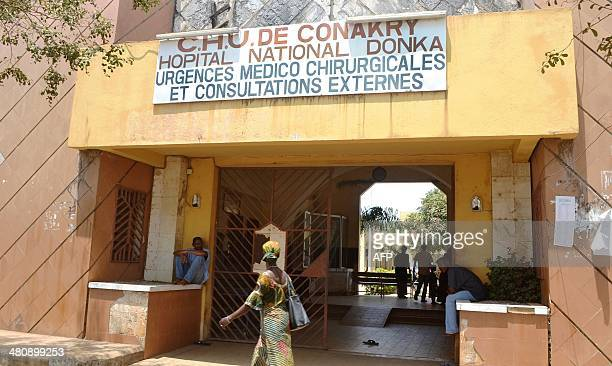 People walk in front of the Donka hospital in Conakry on March 27 2014 Guinea battled to contain an Ebola epidemic threatening neighbouring countries...