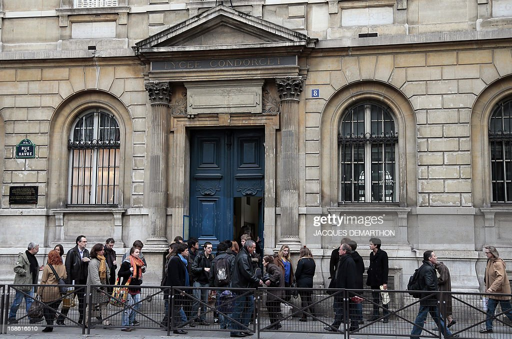 People walk in front of the facade of the Condorcet high school in Paris on December 21, 2012. AFP PHOTO/JACQUES DEMARTHON