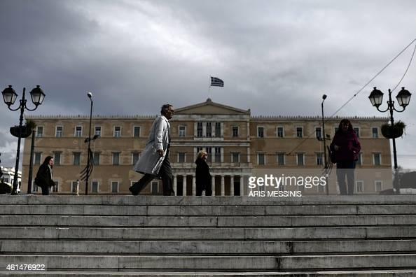 People walk in front of the Greek Parliament in Athens on January 13 2015 Greece could exit the euro by accident Finance Minister Gikas Hardouvelis...