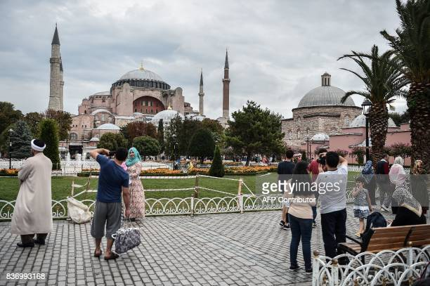 People walk in front of the Hagia Sophia on August 22 2017 during a rainy day in Istanbul / AFP PHOTO / OZAN KOSE