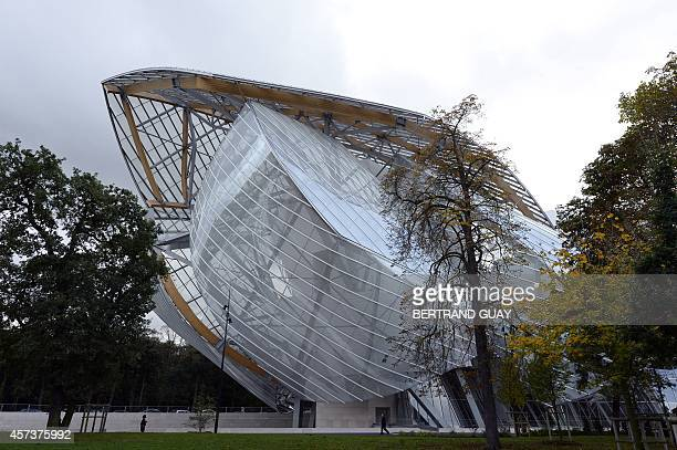 People walk in front of the Louis Vuitton Foundation designed by CanadianAmerican architect Frank Gehry in the Bois de Boulogne in Paris on October...