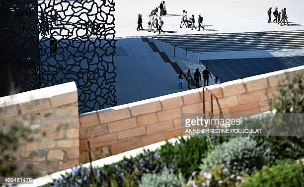 People walk in front of the Museum of European and Mediterranean Civilisations on April 12 2015 in Marseille southern France AFP PHOTO /...
