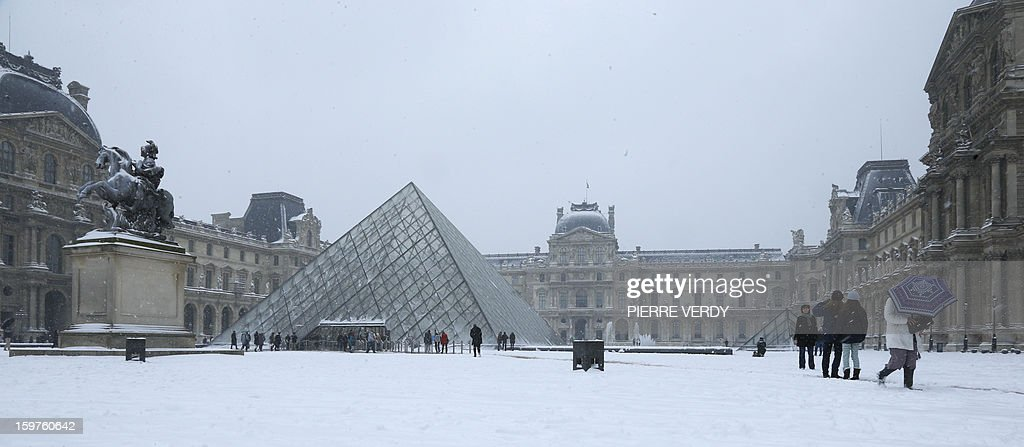 People walk in front of the snow covered Louvre museum in Paris on January 20, 2013. The snow blanketed large parts of northern and southwestern France overnight leading to treacherous road conditions and several fatal car crashes over the weekend. AFP PHOTO PIERRE VERDY