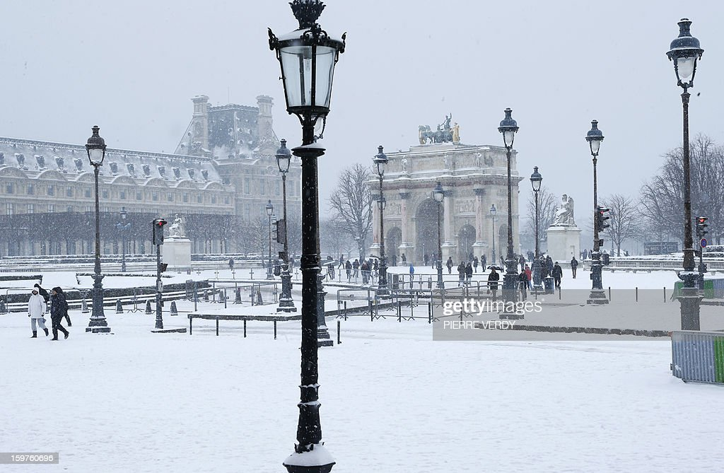 People walk in front of the snow covered Louvre museum in Paris on January 20, 2013. The snow blanketed large parts of northern and southwestern France overnight leading to treacherous road conditions and several fatal car crashes over the weekend.