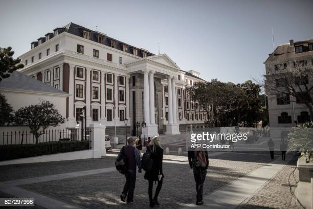 People walk in front of the South African parliament on August 7 2017 in Cape Town A parliamentary vote of no confidence in South African President...