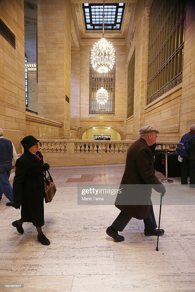 People walk in Grand Central Terminal beneath chandeliers during centennial celebrations on the day the famed Manhattan transit hub turns 100 years old on February 1, 2013 in New York City. The terminal opened in 1913 and is the world's largest terminal covering 49 acres with 33 miles of track. Each day 700,000 people pass through the terminal where Metro-Noth Railroad operates 700 trains per day.
