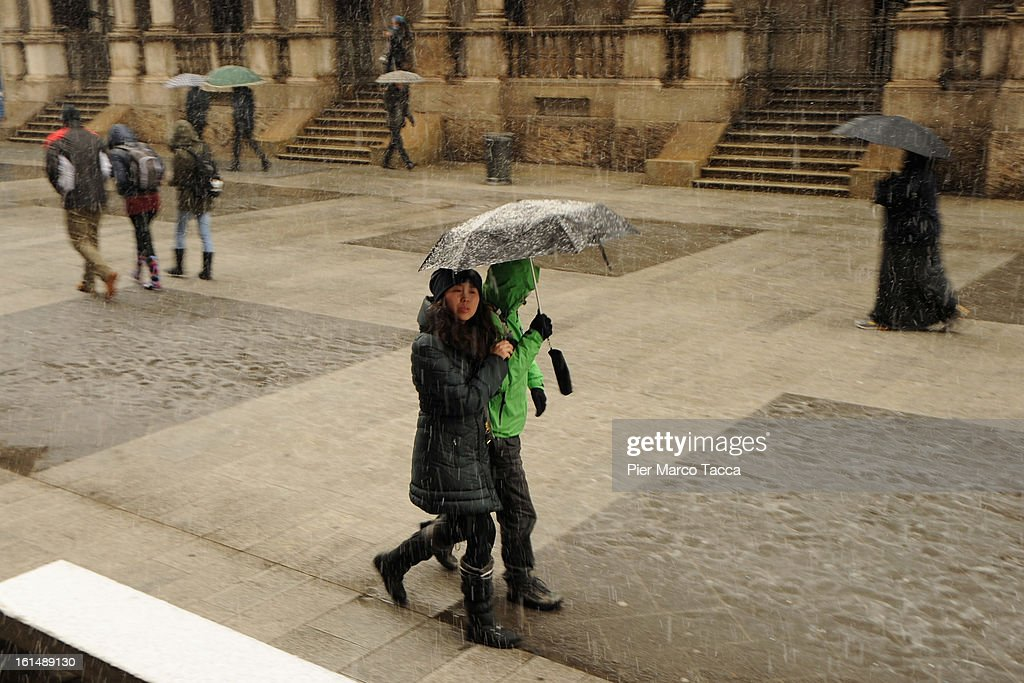 People walk in heavy snow on February 11, 2013 in Milan, Italy.Wind, snow and tempetarture under zero over the country has affected regions from North Italy to South Italy, transports has been affected with train cancellations and road closures.