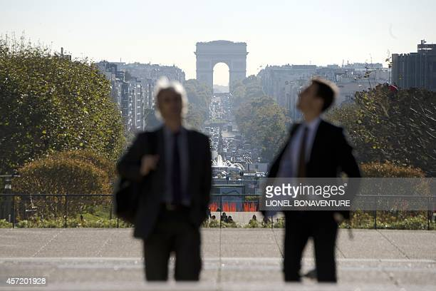 People walk in La Defense business district near Paris on October 14 2014 as the Arc de Triomphe is pictured in the background AFP PHOTO / LIONEL...