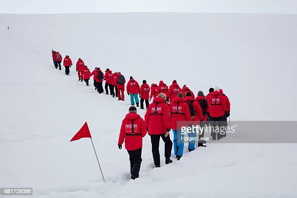 People walk in line on snow bridge
