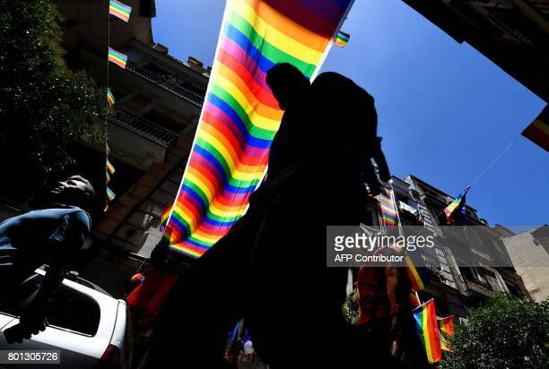 TOPSHOT People walk in Madrid's Chueca district decorated with rainbow flags on June 26 2017 Some three million revellers are expected in the Spanish...