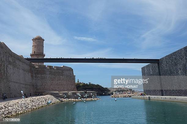 People walk in Marseille southern France on the gangway from Saint Jean fortress to the Mucem which opens officially on June 7 2013 three days after...