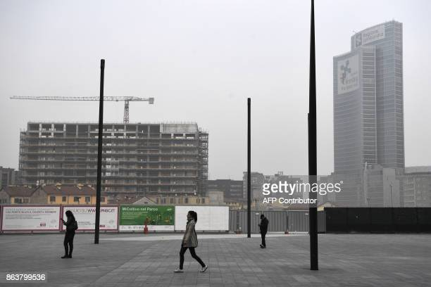 People walk in Piazza Gae Aulenti in the business district in Milan on October 20 as smog has reached alarming levels in northern Italy in recent...