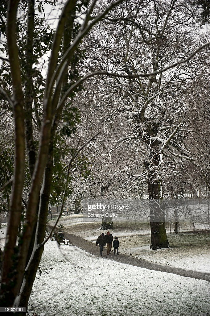 People walk in snow covered Alexandra Park on March 23, 2013 in London, United Kingdom. The UK is facing another day of severe weather disruption, with flood and snow warnings issued in a number of regions across the country.