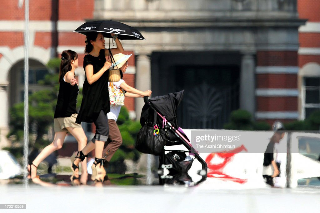 People walk in sweltering heat at Tokyo Station on July 9, 2013 in Tokyo, Japan. Koshu City of Yamanashi reached 39.1 degrees Celsius and two-third of the 927 Japan Meteorological Agency's observation points recorded more than 35 degrees, killing three people by heat disorder.