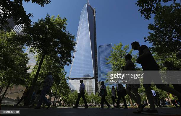 People walk in the 9/11 Memorial plaza as One World Trade Center now the tallest building in the United States continues to be constructed on May 16...