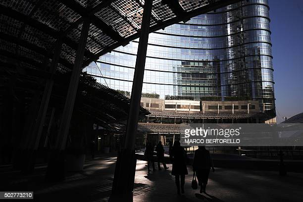 People walk in the business district of Porta Nuova in Milan on December 28 2015 / AFP / MARCO BERTORELLO