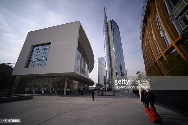 People walk in the business district of Porta Nuova with the Unicredit tower in the background on February 27 2015 in Milan Qatar's sovereign fund...
