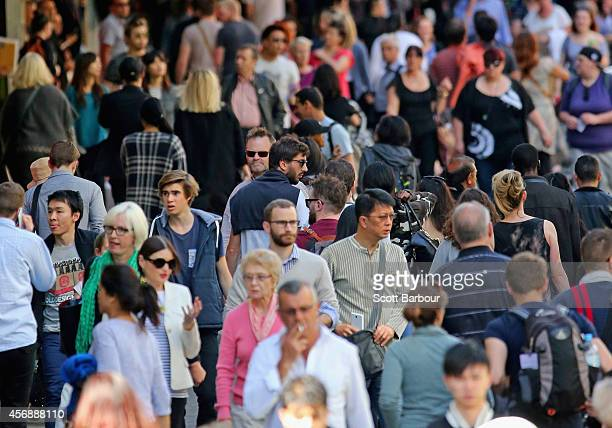 People walk in the city on October 9 2014 in Melbourne Australia Economists expect the Australian jobs figure for September to show an unemployment...