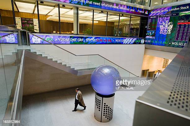 People walk in the foyer of the London Stock Exchange in central London on March 7 2013 AFP PHOTO / LEON NEAL