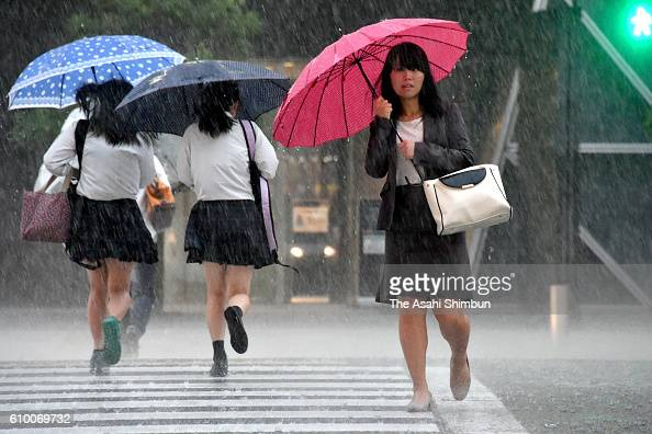 People walk in the heavt rain as Typhoon Malakas hitting the area on September 20 2016 in Nagoya Aichi Japan Japan could suffer from a record number...