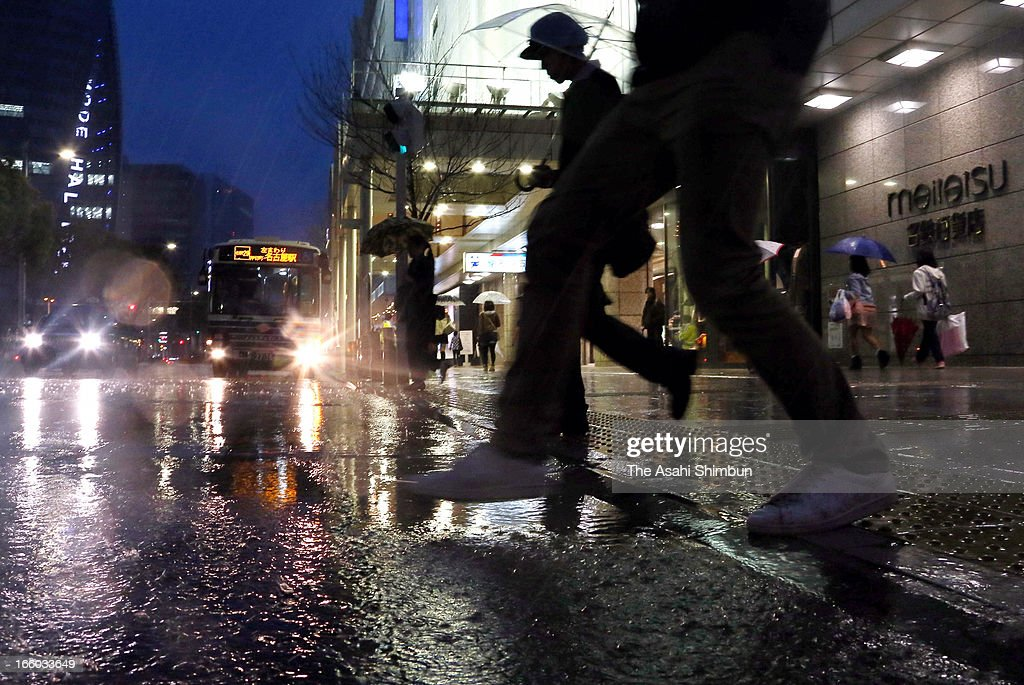People walk in the heavy rain at Nagoya Station on April 6, 2013 in Nagoya, Aichi, Japan. A strong low pressure triggers torrential rain across Japan, the rain falls cherry blossoms in most of area.