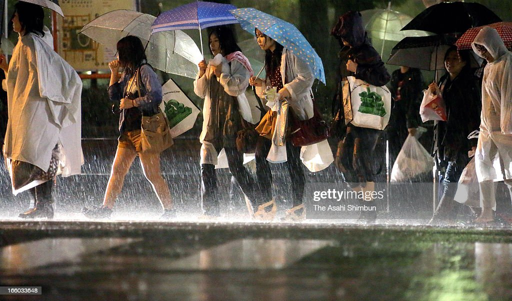 People walk in the heavy rain on April 6, 2013 in Yokohama, Kanagawa, Japan. A strong low pressure triggers torrential rain across Japan, the rain falls cherry blossoms in most of area.
