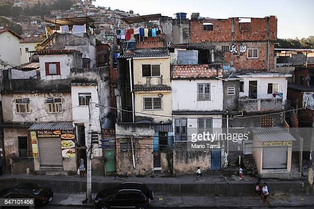 People walk in the Mangueira 'favela' community on July 11 2016 in Rio de Janeiro Brazil Much of the Mangueira favela community sits about a...