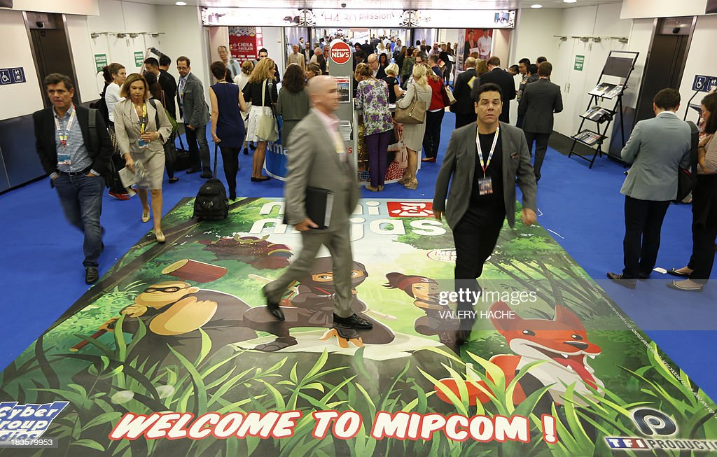 People walk in the 'Palais des Festivals' during the MIPCOM audiovisual trade fair on October 7, 2013 in Cannes, southeastern France. AFP PHOTO / VALERY HACHE
