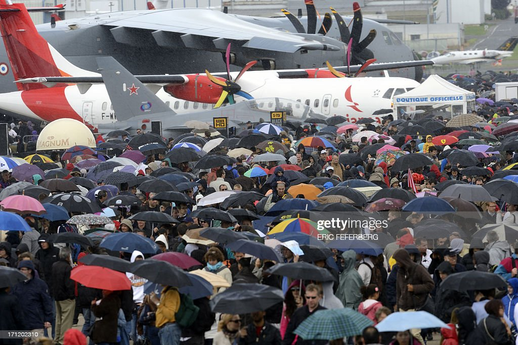 People walk in the rain in front of an Airbus A 400 M and a twin-engine ATR regional airliner, at Le Bourget airport, near Paris, on June 23, 2013 on the last day of the 50th International Paris Air show.