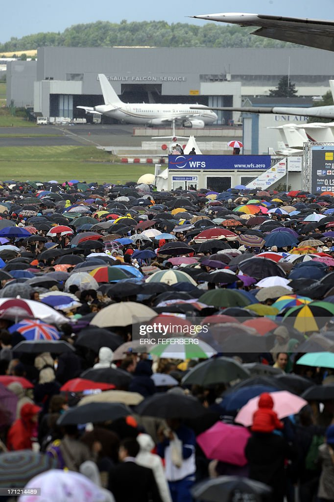 People walk in the rain in front of an Airbus A 400 M and a twin-engine ATR regional airliner, at Le Bourget airport, near Paris, on June 23, 2013 on the last day of the 50th International Paris Air show. AFP PHOTO / ERIC FEFERBERG