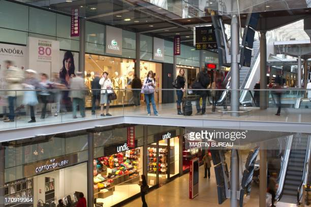 People walk in the shopping gallery of the Gare Saint Lazare railway station in Paris on March 30 2012 in Paris The station reopened after heavy...