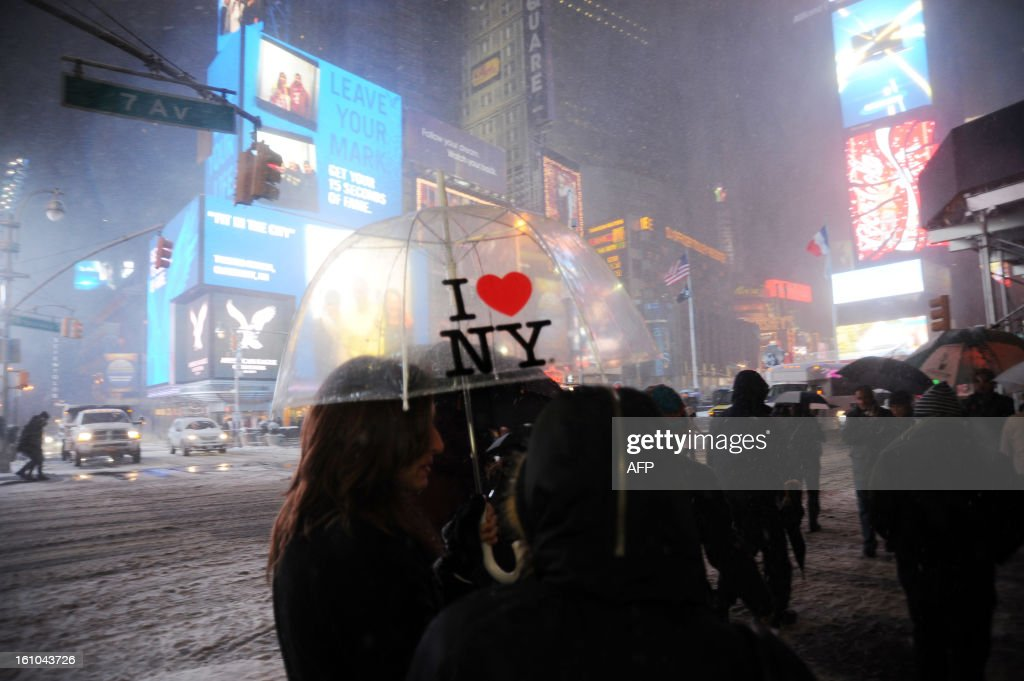 People walk in the snow in Times Square in New York on February 8, 2013 during a storm affecting the northeast US. The storm was forecast to bring the heaviest snow to the densely-populated northeast corridor so far this winter, threatening power and transport links for tens of millions of people and the major cities of Boston and New York. New York and other regional airports saw more than 4,500 cancellations ahead of what the National Weather Service called 'a major winter storm with blizzard conditions' along most of the region's coastline. AFP PHOTO / MEHDI TAAMALLAH