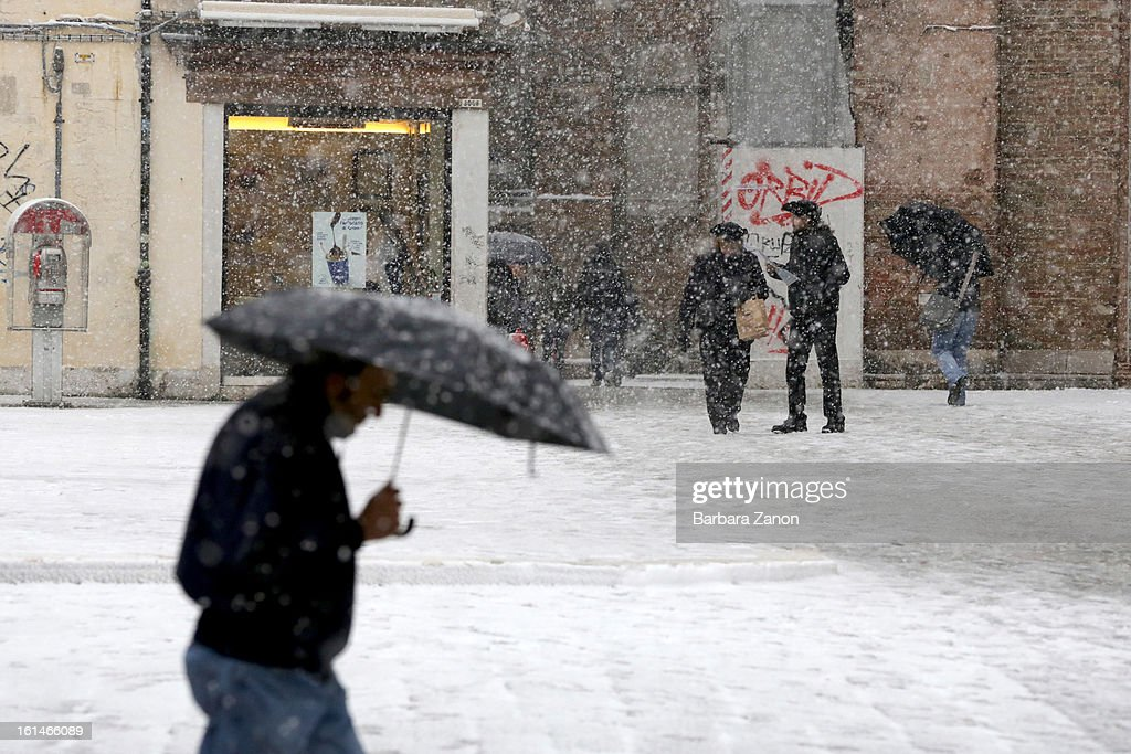 People walk in the snow near Campo dei Frari during heavy snow on February 11, 2013 in Venice, Italy. Heavy snow, rain and wind hit the canals as boats moved commuters across the islands.