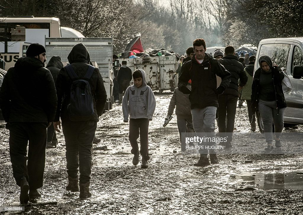 People walk in the so-called 'Jungle' migrant camp in Gande-Synthe where 2,500 refugees from Kurdistan, Iraq and Syria live on February 11, 2016 in Grande-Synthe near the city of Dunkirk, northern France. / AFP / PHILIPPE HUGUEN