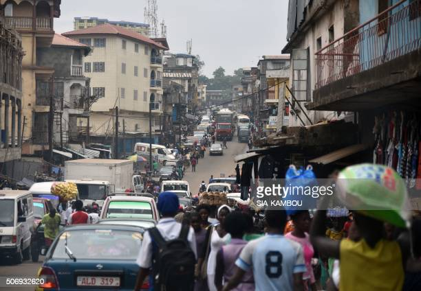 People walk in the street of Freetown on January 22 2016 / AFP / SIAKAMBOU