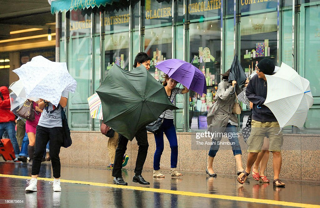People walk in the strong wind as typhoon Man-Yi approaching at Shinjuku Station on September 16, 2013 in Tokyo, Japan. The storm hit land near Toyohashi, Aichi Prefecture, before 8 a.m. and moved along Honshu throughout the day, damaging buildings, disrupting transportation and causing blackouts, three killed and five missing.
