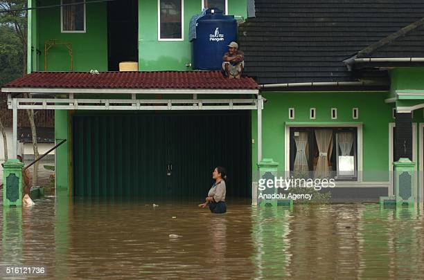People walk in water after heavy monsoon rains that flooded four district in Tasikmalaya West Java Indonesia on March 17 2016 Heavy monsoon rains...