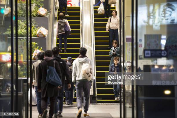 People walk inside an Aeon shopping mall operated by Aeon Mall Co a unit of Aeon Co in Tokyo Japan on Monday April 10 2017 Aeon Co Japan's biggest...