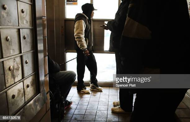 People walk inside of the Farragut Houses a public housing project in Brooklyn on March 16 2017 in New York CityThe budget blueprint President Donald...