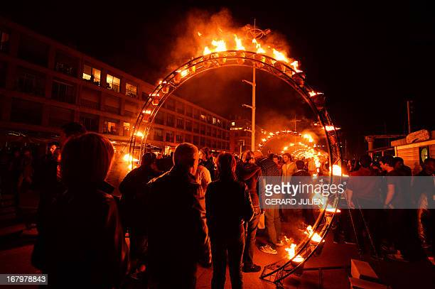 People walk into an art installation displayed during a 'Le Vieux Port entre flammes et flots' lighting night on May 3 at the Port of Marseille as...